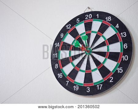 Red and green dart arrow hitting on center target of dartboard.
