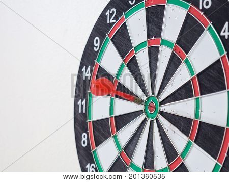 Red dart arrow hitting on center target of dartboard.