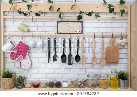 Kitchen utensils on the light brick background. Kitchenware and cooking ingrediants at home. Kitchen background and utensils.