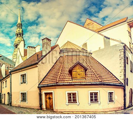 Medieval convent yard and church of the Saint Peter are famous architectural sightseeings in old Riga, Latvia. Image toned for inspiration of retro style