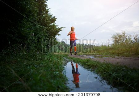 Photo of young girl running along path in park
