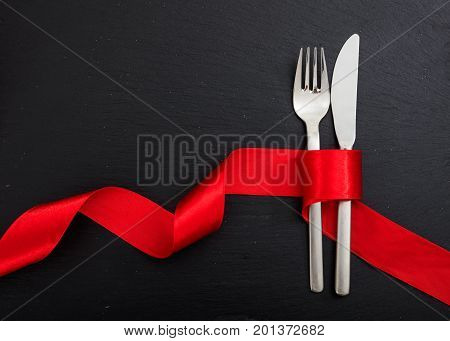 Cutlery And Red Ribbon On Black Background
