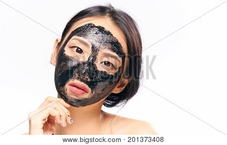 Beautiful young woman on white isolated background in black coal face mask, asian.
