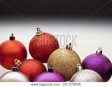 Colorful christmas balls against a gray gradient background.