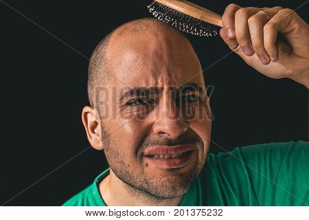 Hair loss concept. Bald man using hair brush on non existent hair against a black background