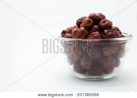 Red dry chinese jujube on glass cup on white background poster