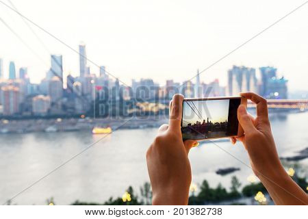 mobile phone with photograph for cityscape of chongqing in cloud sky