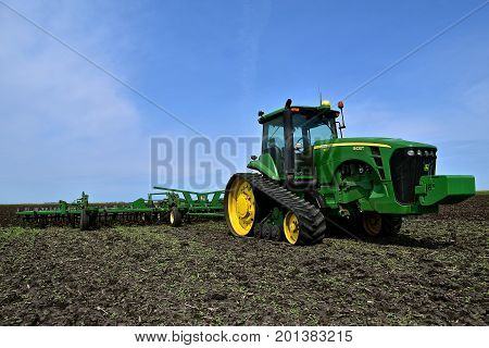 COMSTOCK, MINNESOTA, August 1, 2017: The John Deere 8430T pulling a field cultivator is a product of John Deere Co, an American corporation that manufactures agricultural, construction, forestry machinery, diesel engines, and drive trains