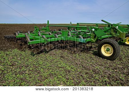 COMSTOCK, MINNESOTA, August 1, 2017: The John Deere field cultivator digging weeds is a product of John Deere Co, an American corporation that manufactures agricultural, construction, forestry machinery, diesel engines, and drive trains