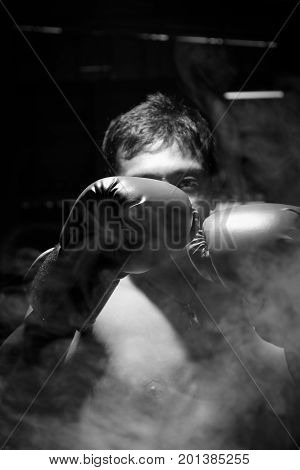 A man wore boxing gloves with smoke for boxing match. Selective focus on boxing gloves. Black and white image.