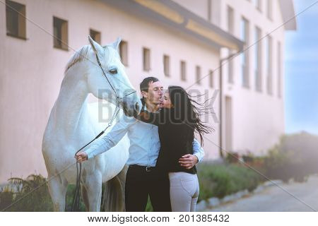 Man and woman with the white horse stay on the horse's club background