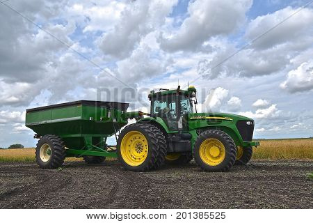 COMSTOCK, MINNESOTA, August 1, 2017: The John Deere 7920 pulling a gravity grain box is a product of John Deere Co, an American corporation that manufactures agricultural, construction, forestry machinery, diesel engines, and drive trains