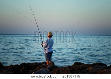 A woman in a hat is fishing with a fishing rod in her hand by the sea coast.