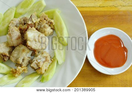 fried pork rib with flour and slice cucumber on plate dipping chili sauce