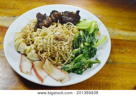 Chinese egg noodles topping slice barbecue pork and braised bone with dumping dressing sweet black sauce on plate
