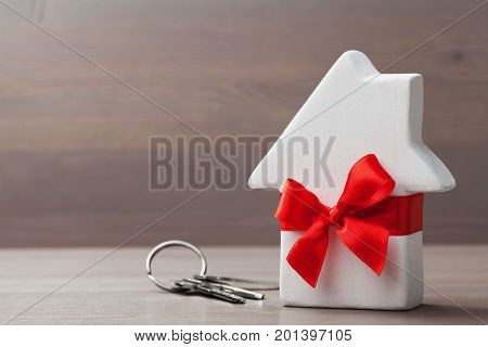 Small white house tied red ribbon and bunch of keys on wooden background. Gift real estate purchase or buying a new home concept.