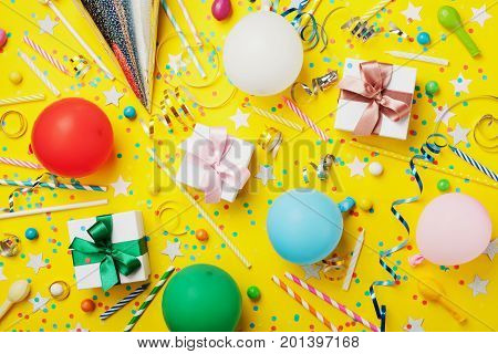 Birthday party background with balloon gift confetti carnival cap star candy and streamer. Flat lay style. Colorful children greeting card.