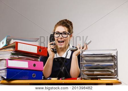 Happy positive shocked business woman smiling sitting working at desk full off documents in binders calling someone.