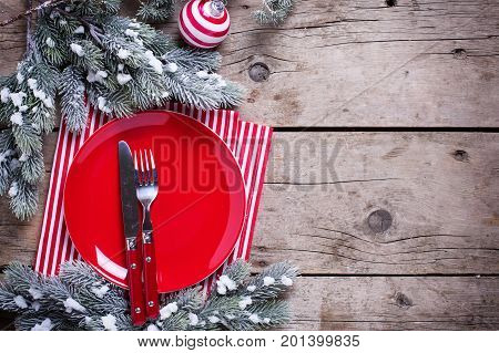 Christmas table setting. Empty red plate knife and fork napkin and ball on rustic wooden background. Top view. Selective focus. Place for text.