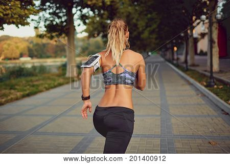 Young athletic girl runner jogging in park in  summer autumn.Back view.