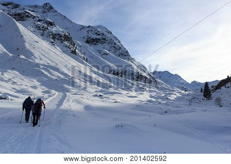 Group of people hiking on wintery snowy path and mountain panorama in Stubai Alps Austria