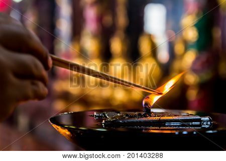 A big oil lamp with hand take a fired joss stick and buddha background