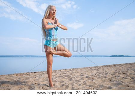 Blonde long haired girl in a blue suit is stretching and doing yoga on a beach in sunlight of the rising sun