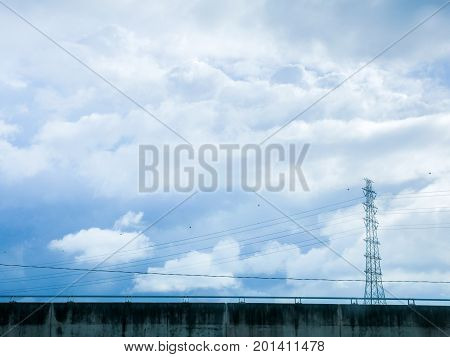 Pylon and high voltage transmission power line in cloudy sky.