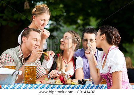In Beer garden - friends Tracht, Dindl and on a table with beer and snacks in Bavaria, Germany