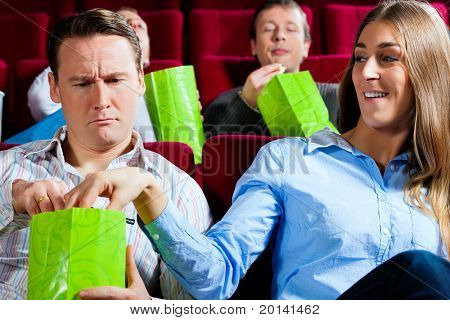 Couple in cinema watching a movie; they eating popcorn