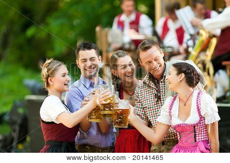 In Beer garden in Bavaria, Germany - friends in Tracht, Dindl and Lederhosen and Dirndl standing in front of band