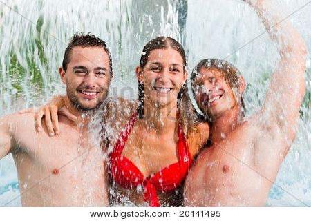 Three young people - woman and two men - at a public swimming pool standing under a water gadget