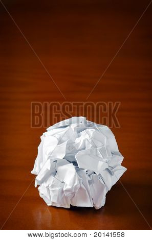Ball of smashed sheet of paper over wooden table
