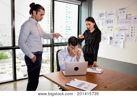 businessman is nervous and put his hand on head because his boss and colleague very agry and Pointing fingers at him. The concept of business mistakes.