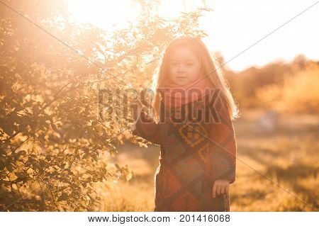 Smiling baby girl 3-4 year old wearing stylish autumn jacket outdoors. Looking at camera. Posing in park. Childhood.