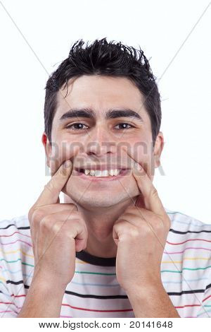 Young man with a funny face with a forced smile (isolated on white)