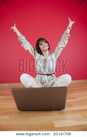 Happy woman using the laptop computer at her house floor, next to a red wall (selective focus)