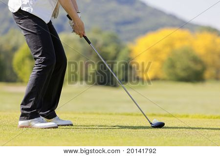 Close up of senior female golf player teeing off ball on beautiful golf course.