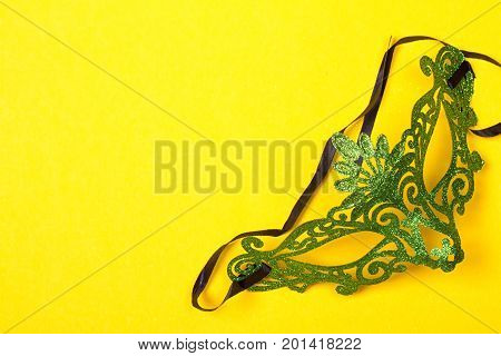 Green mardi gras mask on a bright yellow background