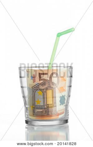 Financial concept: drinking a 50 euro bill in a glass and a straw