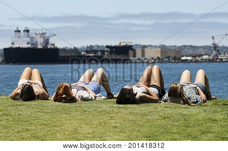 SAN DIEGO, CALIFORNIA, JUNE 9: Seaport Village on June 9, 2017, in San Diego, California. A Quartet of Young Woman Sunning Themselves at Embarcadero Park in Seaport Village in San Diego.