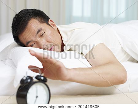 asian man lying in bed trying to stop ringing alarm clock.