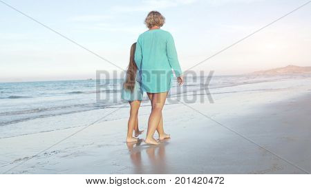 Mother with daughter strolling on seashore in sunny day.