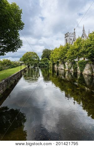 Galway Ireland - August 3 2017: Corrib River arm is channeled between walls in park over which Saint Vincents Convent of Mercy towers show. Cloudscape and lots of green.