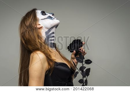 Woman with scary Halloween skeleton makeup holding black rose flower over gray background