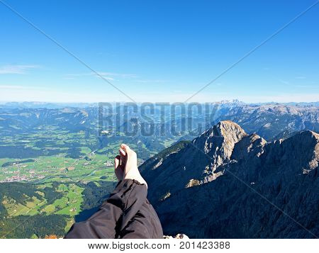 Naked Male Sweaty Legs In Dark Hiking Trousers Take A Rest On Peak Of Mountain Above Spring Valley.