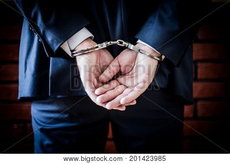 Businessman With Hands On The Back And Handcuffs On. Arrested For Corruption And Crime In Business W
