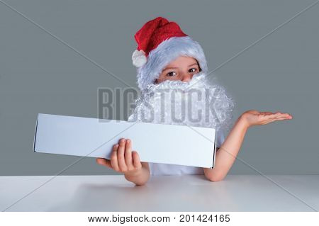 Little Santa Claus Holding In His Right Hand A White Box, Left Hand Turned Palm Up. He Is Sitting At