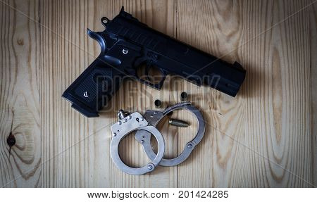 Black Pistol Gun With Silver Handcuffs And Golden Bullet Shells Laying On A Wooden Background Used B