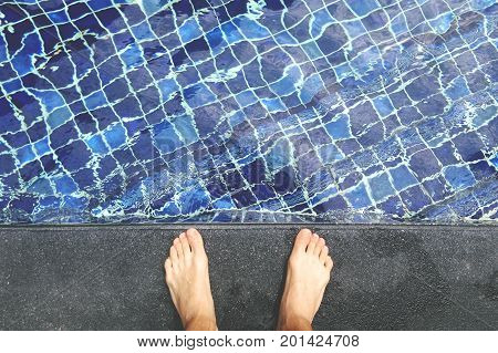 View From Above on Bare Male feet at Swimming Pool Side. Thailand